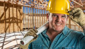 Helpful Contractor in Hard Hat Holding Floor Plans At Construction Site. Smiling Contractor in Hard Hat Holding Floor Plans At Construction Site Stock Photography