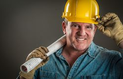 Friendly Contractor in Hard Hat Holding Floor Plans. Smiling Contractor in Hard Hat Holding Floor Plans With Dramatic Lighting Royalty Free Stock Photo