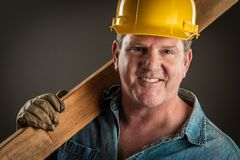 Smiling Contractor in Hard Hat Holding Plank of Wood i royalty free stock photo