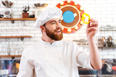 Smiling cook cheif holding slice of yellow bell pepper Stock Image