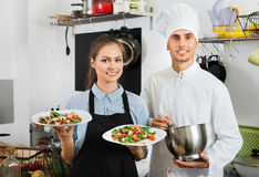 Smiling cook giving to waitress ready to serve salad Royalty Free Stock Images
