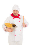 Smiling cook man holding pan filled with raw macaroni wearing wh Royalty Free Stock Photo