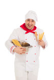 Smiling cook man holding pan filled with raw macaroni wearing wh Stock Photos