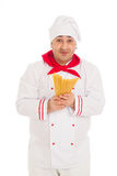Smiling cook man wearing white uniform holding raw macaroni. In the studio over white background Royalty Free Stock Image