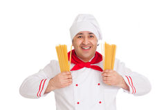 Smiling cook man wearing white uniform holding raw macaroni in t. He studio over white background Stock Image