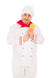 Smiling cook man wearing white uniform holding raw macaroni in t. He studio over white background Stock Photography