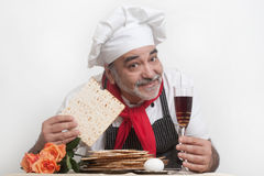 Smiling cook with matza. Beautiful roses and wine Stock Images