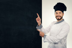 smiling cook pointing on blank blackboard. copy space royalty free stock photo