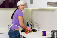 Smiling cook washing the dishes in the kitchen Royalty Free Stock Photos