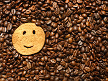 Smiling  cookie on coffee beans background. Simple smiling cookie on roasted coffee beans background Royalty Free Stock Image