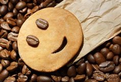 Smiling cookie on package label with roasted coffee beans. Close up of single smiling cookie on top of mint wrapping paper on roasted coffee beans Stock Photography