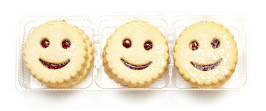 Smiling cookies. In plastic box isolated on white Stock Images
