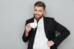 Smiling cool bearded man in suit holding cup of coffee Stock Photos
