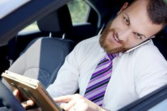 Smiling cool young business man at work in car with technology Stock Image