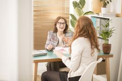Smiling corporate advisor supporting employee. Smiling corporate advisor supporting a burnt out employee in the office royalty free stock image