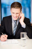 Smiling corporate guy attending phone call Royalty Free Stock Photo