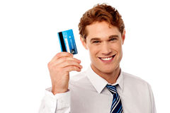 Smiling corporate guy holding credit card royalty free stock image