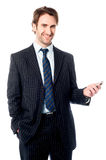 Smiling corporate head holding out cellphone Royalty Free Stock Photo