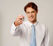 Smiling corporate holding a key Royalty Free Stock Image