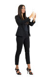 Smiling corporate woman in formal black suit taking photo with cellphone. Full body length portrait isolated over white studio background Royalty Free Stock Photos