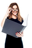 Smiling corporate woman holding open folder Stock Photo