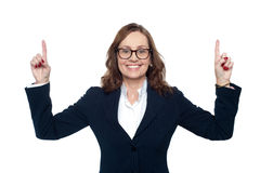 Smiling corporate woman pointing upwards Stock Photos
