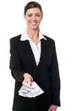 Smiling corporate woman showing british pound Stock Photo