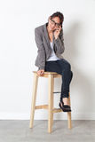 Smiling corporate woman working with cell phone sitting on stool Stock Photos