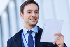 Smiling correspondent is looking into his writing Stock Images
