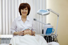 Smiling cosmetician does to patient facial massage. In beauty salon stock photos