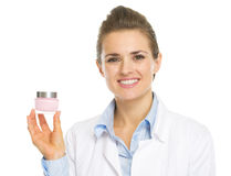 Smiling cosmetologist woman showing cream bottle Royalty Free Stock Photos