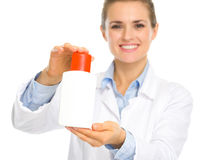 Cosmetologist woman showing sun block creme Stock Image