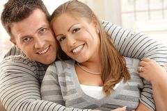 Smiling couple. Portrait of smiling couple embracing looking at camera at home royalty free stock photos