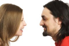 Smiling couple. Young adult couple smiling at each other over white background Stock Photography