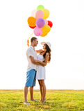 Smiling couple with air balloons outdoors Stock Image