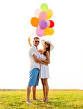 Smiling couple with air balloons outdoors Stock Photos