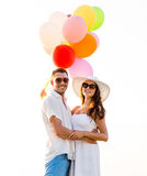 Smiling couple with air balloons outdoors Royalty Free Stock Images