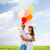 Smiling couple with air balloons outdoors Royalty Free Stock Photo