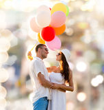 Smiling couple with air balloons outdoors Stock Images