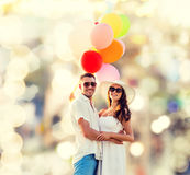 Smiling couple with air balloons outdoors Royalty Free Stock Photos