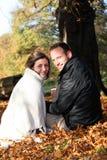Smiling couple amongst autumn leaves Stock Photo