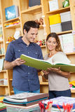 Smiling Couple Analyzing Large Book In Store Stock Photos