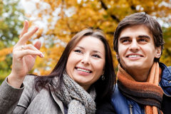 Smiling couple autumn pointing Stock Images