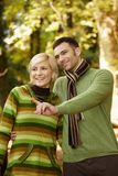 Smiling couple on autumn walk. Happy couple on autumn walk in park, men showing something to smiling women Royalty Free Stock Images
