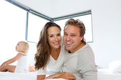 Smiling couple with baby girl in bed Royalty Free Stock Image