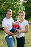 Smiling couple with baby in park Stock Images