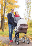 Smiling couple with baby pram in autumn park Royalty Free Stock Photo