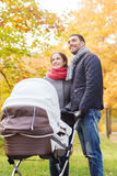 Smiling couple with baby pram in autumn park Royalty Free Stock Photography