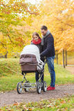 Smiling couple with baby pram in autumn park Stock Images
