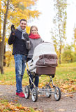Smiling couple with baby pram in autumn park Royalty Free Stock Images